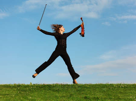 girl with violin jumps on grass against  sky photo