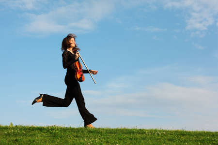 girl with violin runs on grass against  sky, side view photo