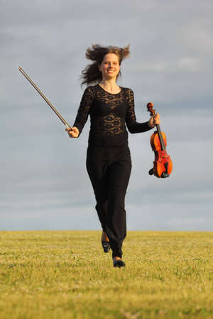 girl with violin runs on grass against  sky, front view photo