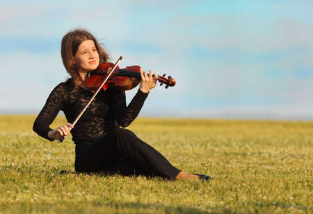 girl sits on grass and plays violin against  sky photo