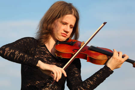 girl plays violin against  sky photo