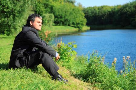 resting businessman sitting on river bank photo