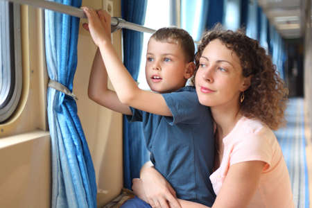 mother and son in train`s corridor looks in window photo