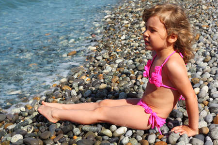 wet suit: little girl sits on stone beach Stock Photo