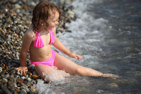 little girl sits ashore in waves photo