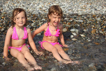 two little girls sit ashore in water photo