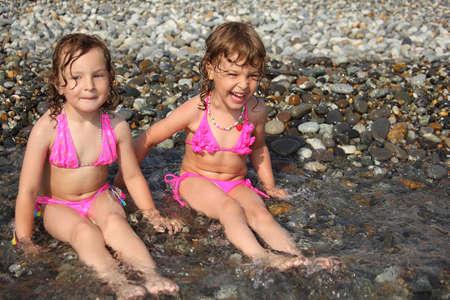 two little girls sit ashore in water photo
