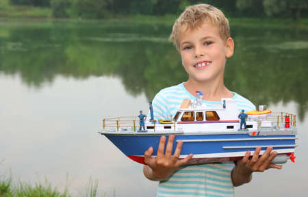 ashore: boy with toy ship in hands ashore