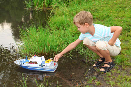 pool preteen: boy sends toy ship in floating