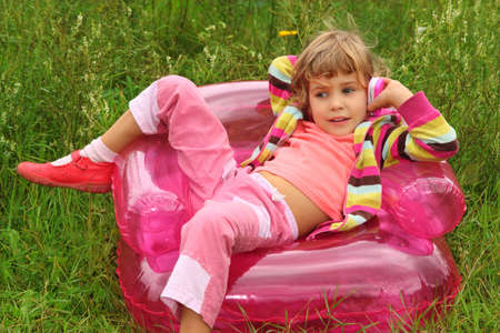 little girl sits talks by toy phone in inflatable armchair  on lawn photo