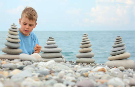 boy and stone stacks on pebble beach photo