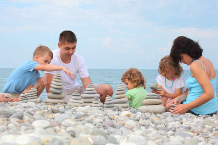 family with three children builds  stone stacks on pebble beach photo