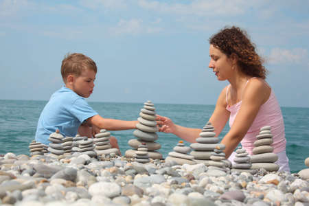 mother and son builds  stone stacks on pebble beach photo