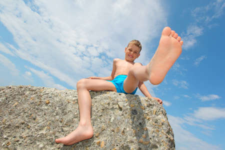 hot boy: boy sits on rock, bottom view