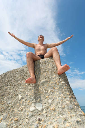 man in slips sits on rock, bottom view photo