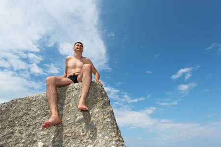 man in slips sits on rock, bottom view, horizontal shot photo