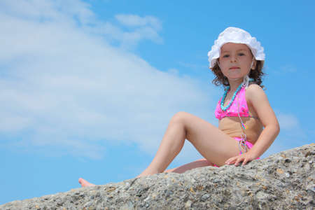 bikini top: little girl in swimsuit sits on rock against sky Stock Photo