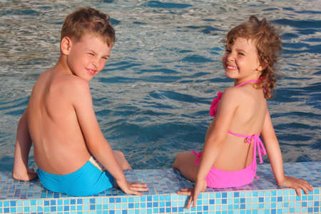 boy and girl sit on border of pool photo