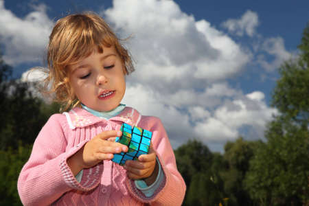 little girl with magic earth cube outdoor in summer photo