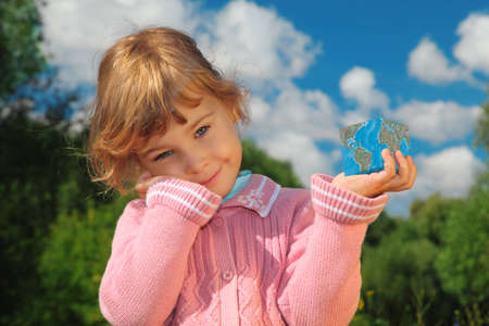 little girl with Earth cube outdoor in summer photo