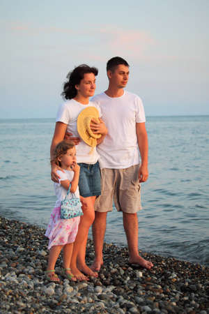 family with little girl standing on stone evening beach photo
