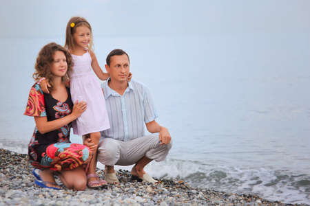 Happy family with little girl on stony beach photo