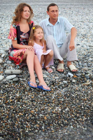 Happy family with little girl sitting on stony beach photo