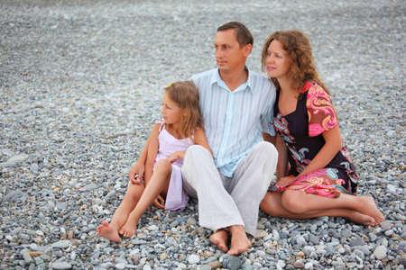 shingle beach: Happy family with little girl sitting on stony beach  Stock Photo