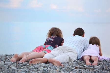 shingle beach: Happy family with little girl lying on stony beach, lying back
