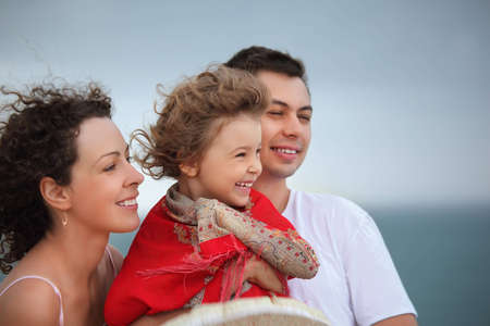 protects: young man and beautiful woman protects little girl from wind on seacoast Stock Photo