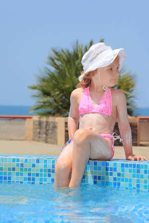 little girl barefoot: pretty little girl smeared with cream for sunburn wets feet water in pool against sea Stock Photo