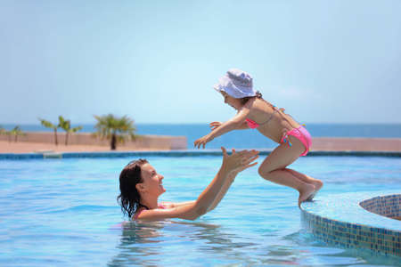 enjoy: beautiful woman catches little girl jumping in pool against sea
