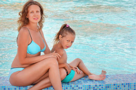 bathing suits: beautiful woman with little girl sit near in pool