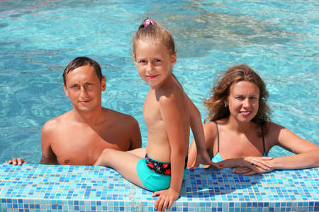 Happy family with little girl bathe in pool, daughter sits near pool Stock Photo - 7831177