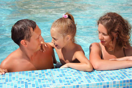 Happy family with little girl bathe in pool Stock Photo - 7831141
