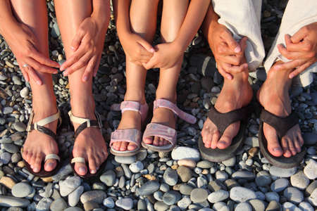 lot of legs and hands on the stones. family with girl photo