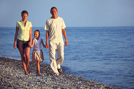 pebblestone: familywith girl walks along sunset sea beach