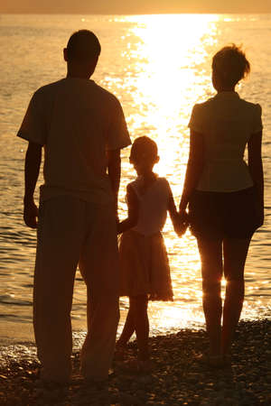 against the sun: three silhouettes against glossing sea. Parents and daughter. Stock Photo