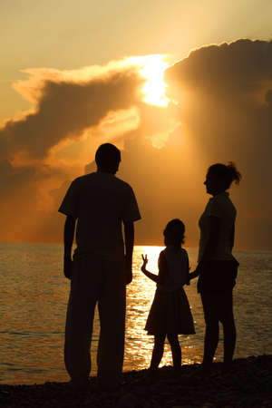 three silhouettes against glossing sea. Parents and daughter. photo