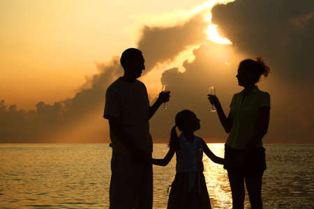 three silhouettes against glossing sea. Daughter between parents. Parents holding glasses Stock Photo - 7790944