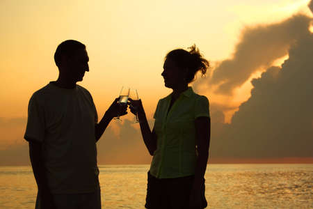 Man and woman clink glasses. Silhouettes against sea. photo