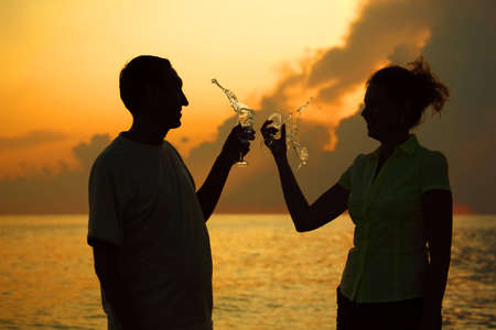 Man and woman clink glasses. Splashes of wine from glasses. Silhouettes against sea. photo