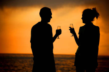 Silhouettes of man and woman with glasses on sea sunset photo