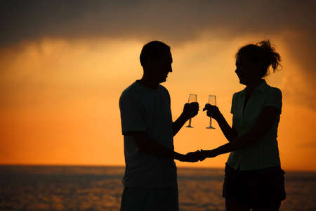 Silhouettes of man and woman with glasses on sea sunset Stock Photo - 7829741