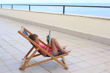 little boy reads in lounge on veranda photo