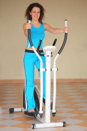 smiling young woman on training apparatus, full body photo