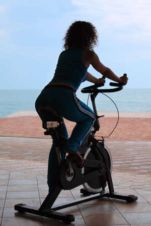 silhouette of girl on bicycle training apparatus outdoor on beach photo
