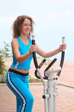 smiling girl on training apparatus outdoor on beach photo