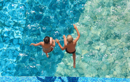 blue top: Two children jump in water,  top view Stock Photo