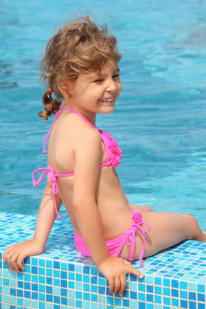 bathing suits: little girl sits on border of pool